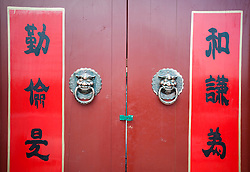 Detail of traditional red wooden house door in a Beijing hutong
