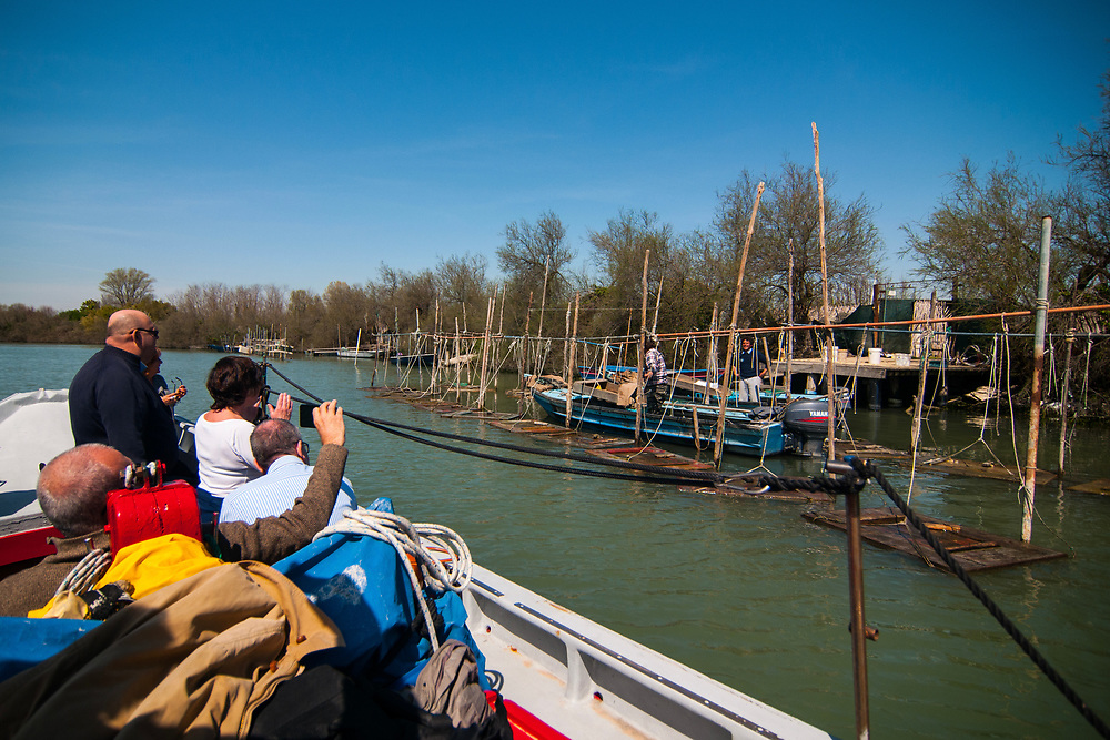 """VENICE, ITALY - APRIL 2018. <br /> Tourists arrive at the """"cason"""", the typical temporary house of the fishermen of the Venetian lagoon, of Emiliano, a moecante (crabs fisherman). Moeche, in all Italy, are fished just in the Venetian lagoon, and just in the months of april-may and september."""