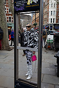 Framed in the missing panels of a map of the capitals West End theatre district, a woman fashionista wearing a monochrome outfit stands outside in the street before an event held at the National Portrait Gallery during London Fashion Week, on 17th February 2020, in London, England.