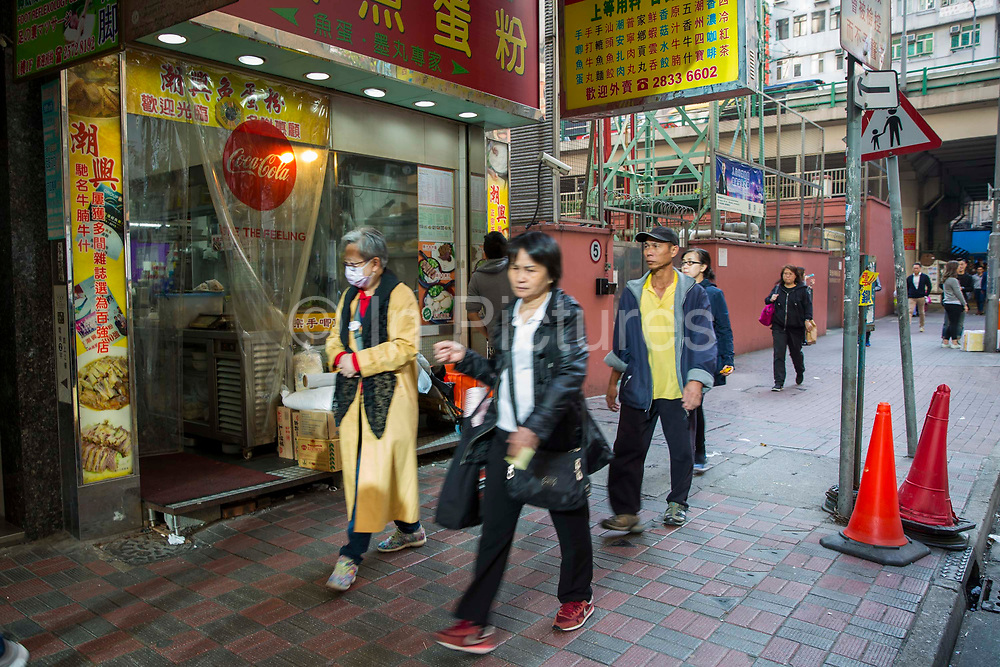 Pedestrians commuting and shopping on the streets of Hong Kong.