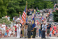 Officer Young stops to salute our American flag before leading the 4th of July parade through the town of Gilmanton Saturday morning.   (Karen Bobotas/for the Laconia Daily Sun)