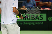 Tennis player in white clothes ready to serve a ball