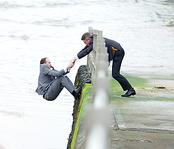UKIP 2015 Spring Conference at the Winter Gardens Margate, Great Britain <br /> 28th February 2015 <br /> <br /> <br /> Sam Gould <br /> UKIP PPC Caerphily <br /> writing a message to Nigel Farage on the beach outside the conference venue. <br /> <br /> being pulled up by Gawain Towler <br /> <br /> <br /> Photograph by Elliott Franks <br /> Image licensed to Elliott Franks Photography Services