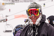 Snowboarder with snowy sideburns in lift line at Whitefish Mountain Resort in Whitefish, Montana, USA