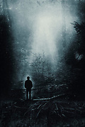 Dark forest scenery on a misty morning with a single man facing the coming light - black and white image - photomanipulation