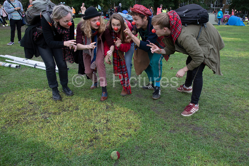 Extinction Rebellion activists wearing red noses play a game where they pretend to creep up on a tennis ball as the climate camp at Vauxhall is cleared on 15th October 2019 in London, England, United Kingdom. Extinction Rebellion is a climate change group started in 2018 and has gained a huge following of people committed to peaceful protests. These protests are highlighting that the government is not doing enough to avoid catastrophic climate change and to demand the government take radical action to save the planet.