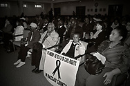 """MAY 9, 2011 - MINEOLA, NY: Young boy, Ramel Smith Jr sitting with sign with ribbon drawn in middle and the message: """"We Mourn the Death of Civil Rights in Nassau County"""" at Nassau County Legislature's public hearing on Legislative Redistricting. S At Nassau County Executive and Legislative Building, 1550 Franklin Avenue, Mineola, New York, USA on May 9, 2011"""