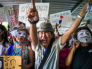 """02 JUNE 2013 - BANGKOK, THAILAND:  An anti-government protester screams as he marches through the skywalk system in Bangkok. The so called White Mask protesters are strong supporters of the Thai monarchy. About 300 people wearing the Guy Fawkes mask popularized by the movie """"V for Vendetta"""" and Anonymous, the hackers' group, marched through central Bangkok Sunday demanding the resignation of Prime Minister Yingluck Shinawatra. They claim that Yingluck is acting as a puppet for her brother, former Prime Minister Thaksin Shinawatra, who was deposed by a military coup in 2006 and now lives in exile in Dubai.    PHOTO BY JACK KURTZ"""