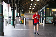 A man jogs through Flinders Street Station during COVID-19 in Melbourne, Australia. Victoria has recorded 14 COVID related deaths including a 20 year old, marking the youngest to die from Coronavirus in Australia, and an additional 372 new cases overnight. (Photo by Dave Hewison/Speed Media)