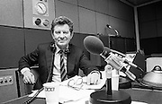 The veteran BBC broadcaster Richard Baker (same name as the photographer of this picture) is seen in a Radio 3 studio in Langham Place, in central London. With glasses at hand and programme notes on his console with microphones pointing to his face, Baker is looking to camera with a pair of old-fashioned earphones around his neck. Richard Baker OBE (born 1925) started at the BBC as an announcer and presented many classical music programmes on both television  and radio, including for many years the annual live broadcast from the Last Night of the Proms but he's best known as a newsreader for the BBC News from 1954 to 1982 and the long-running Your Hundred Best Tunes for BBC Radio 2 on Sunday nights.