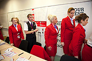 Virgin Atlantic air stewardess training classroom at The Base training facility in Crawley. Potential hostesses are put through a gruelling 6 week training program, during which they are tested to their limits. With exams every day requiring an 88% score to pass. The Base is a modern environment for a state of the art airline training situated next to Virgin Atlantic's HQ. These trainees are just one week away from getting their 'wings' and taking their first commercial flights as fully trained flihgt attendants.