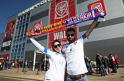Slovakia fans pose for a picture with a half and half scarf prior to the match