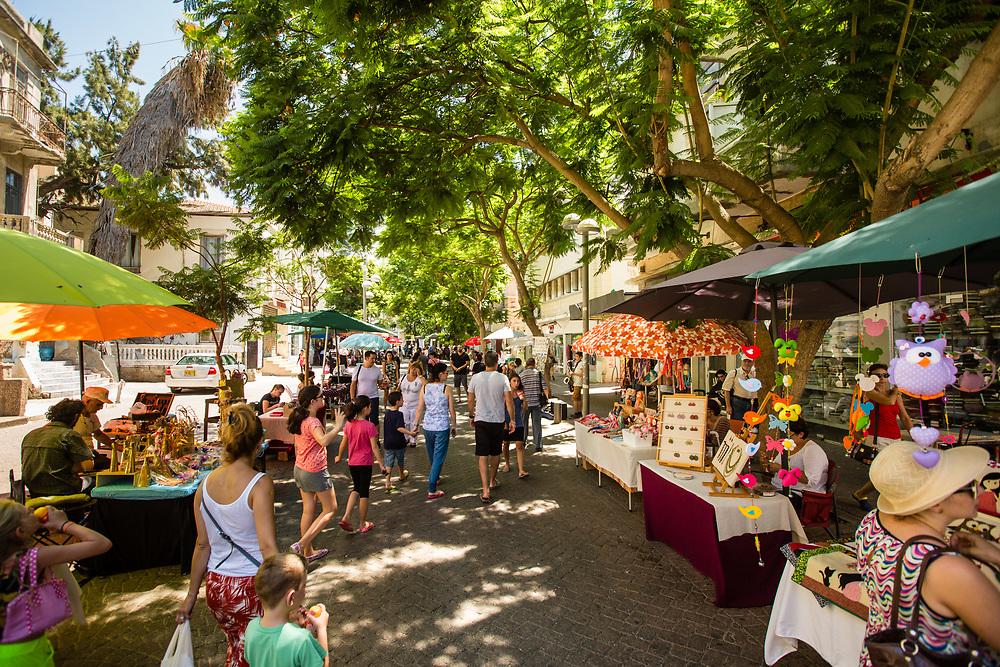 People attend the Nachalat Binymain Arts and Crafts Market near Shuk Hacarmel in Tel Aviv's Kerem HaTeimanim neighborhood