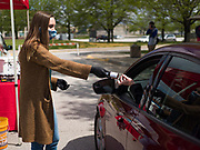 06 MAY 2020 - DES MOINES, IOWA: JORDYN PRINCE, from Cedar Ridge Winery and Distillery, hands a bottle of  hand sanitizer to a person in a drive through at Principal Park, the stadium for the Iowa Cubs, the minor league baseball team affiliated with the Chicago Cubs. Two months after the start of the COVID-19 pandemic Iowa retailers still can't keep everyday items like hand sanitizer, toilet paper, and alcohol based cleaning supplies in stock. Many of the artisan distilleries in Iowa have started making and distributing free hand sanitizer.       PHOTO BY JACK KURTZ