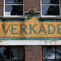 Nederland, Zaandam , 5 juli 2013.<br /> Wandeling door de binnenstad van Zaandam.<br /> Starten bij De Werf aan de Oostzijde. Daarvandaan kun je lopen op een soort boulevard tussen de flats en het water. De eerste stop is De Fabriek, filmhuis en eetcafé met terras aan de Zaan met uitzicht op de sluis. Daarna de sluis zelf.<br /> Dan langs het winkelgebied richting de Koekfabriek: Het oude Verkade pand dat is verbouwd en waar nu de bieb en sportschool en restaurant etc. in zitten.<br /> (Dat is aan de overkant van het startpunt) en misschien nog de Zwaardemaker meepakken aan de Oostzijde. Dat is een oud pakhuis die Rochdale enige jaren geleden heeft verbouwt tot appartementen met een stukje Nieuwbouw.<br /> Ook doen: het Russische buurtje vlakbij de Zaan. Dit jaar staat Rusland in de schijnwerpers en Zaandam heeft een speciale band met Rusland, vanwege het Czaar Peterhuisje en de Russische buurt. <br /> Op de foto: Op de Verkade fabriek de letters Verkade.<br /> Foto:Jean-Pierre Jans