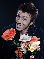 studio portrait on black background of a funny expressive caucasian man offering flowers cheerful seductor