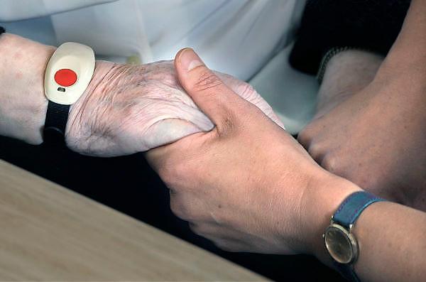 Nederland, Nijmegen, 16-5-2011Hand van oudere en jongere. vergrijzing, zorg, hulp, geriatrie, verpleeghuis, veroudering. De oudere vrouw heeft een polsband met alarm om.Foto: Flip Franssen