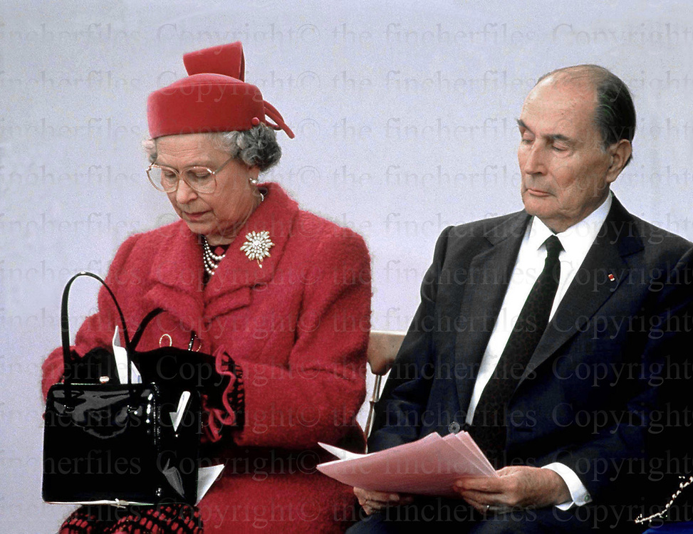 President Mitterrand of France peers curiously into HM The Queen's handbag during the opening ceremony of the Euro tunnel in May 1994. Photographed by Jayne Fincher