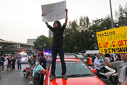 © Licensed to London News Pictures. 26/05/2014. An anti-coup protestor stand on top of a taxi holding an pro democracy banner following a Anti-Coup protest in Bangkok Thailand. Today Thailand's King formally approved Thai army chief General Prayut Chan-O-Cha as head of the nation's new military junta.  Photo credit : Asanka Brendon Ratnayake/LNP