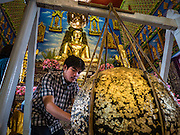 30 JANUARY 2016 - NONTHABURI, NONTHABURI, THAILAND: People make merit by applying gold leaf to a ball in the viharn, or main prayer hall, at Wat Bua Khwan, a large Buddhist temple in Nonthaburi, north of Bangkok, Thailand.        PHOTO BY JACK KURTZ