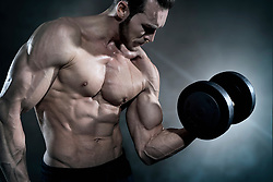 Muscular man doing exercise with dumbbells
