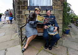 © Paul Thompson licensed to London News Pictures. 16/05/2015. Haworth, West Yorkshire, UK. A woman reading the Victory edition of Picture Post magazine during Haworth 1940s weekend, an annual event in which people dress in period costume and visit the village of Haworth to relive the 1940s.  Photo credit : Paul Thompson/LNP