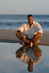 Man seated by calm water on the ocean in East Hampton, NY