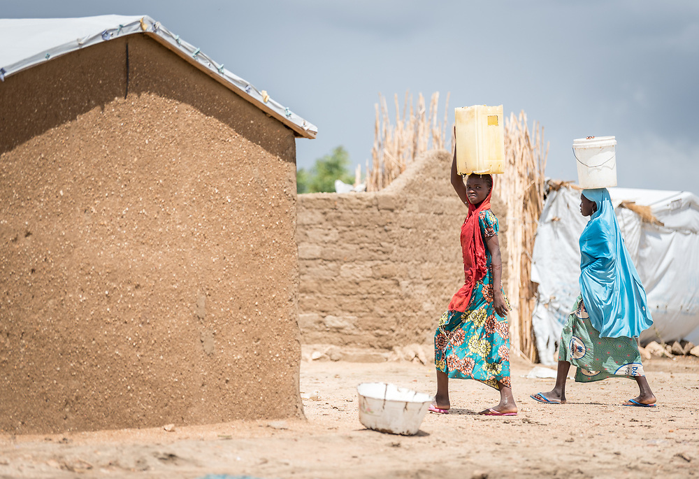 30 May 2019, Mokolo, Cameroon: Women carry their jerry cans through the Minawao camp for Nigerian refugees. The Minawao camp for Nigerian refugees, located in the Far North region of Cameroon, hosts some 58,000 refugees from North East Nigeria. The refugees are supported by the Lutheran World Federation, together with a range of partners.