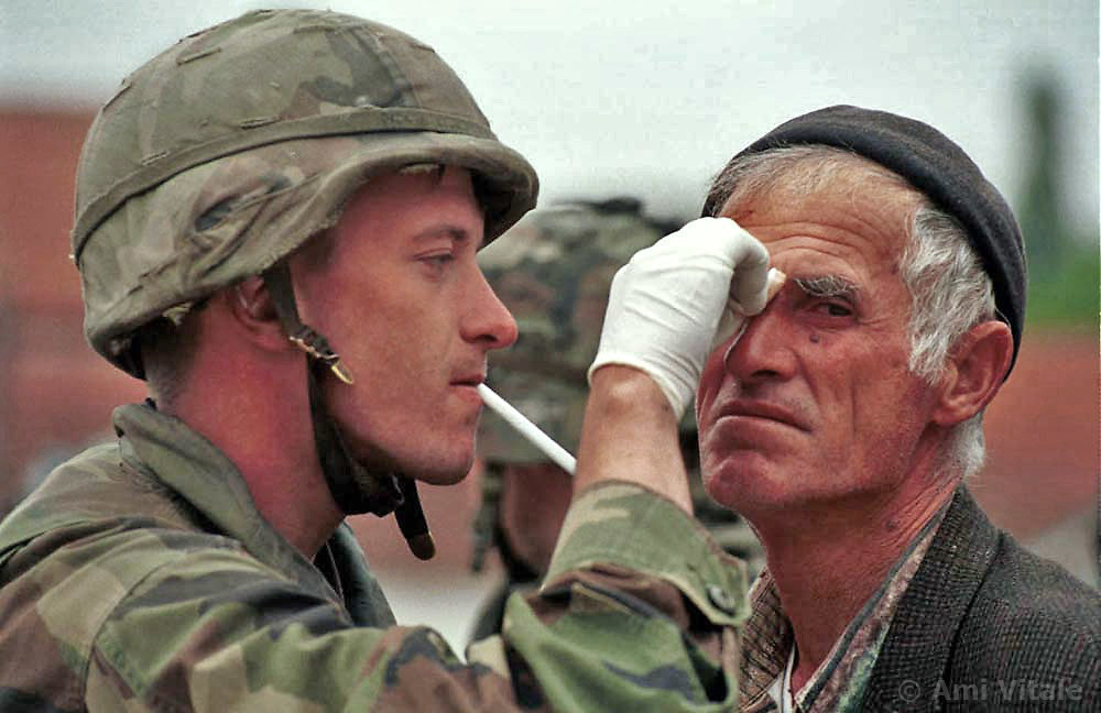 John Holmstrom, 21, from Calumet, Michigan treats ethnic Albanian Isuf Rrahmani, 61, after he was attacked by angry Serbians who were fleeing their village of Zegra in Kosovo Thursday, June 24, 1999. (photo by Ami Vitale)