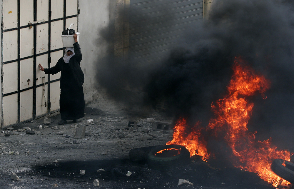A Palestinian woman walks past burning tires after clashes between Palestinians and Israeli border police erupted in the West Bank refugee camp of Shuafat, in East Jerusalem, on March 3, 2008. Clashes broke out across the West Bank on Monday between Israeli troops and Palestinian youths protesting Israel's Gaza operations.