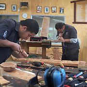 Men carving watched by tourists at Te Puia's Carving School, Rotorua, New Zealand,  New Zealand. .Te Puia is the premier Maori cultural centre in New Zealand - a place of gushing waters, steaming vents, boiling mud pools and spectacular geysers. Te Puia also hosts National Carving and Weaving Schools and  daily maori culture performances including dancing and singing. Rotorua, 9th December 2010 New Zealand.  Photo Tim Clayton..