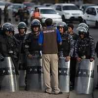 Demonstrations against the irregularities and fraud in the elections of Nov 26 in Honduras were repelled by the Honduran Army. Riot police refused to repress demonstrations, a move that was welcomed, but when a new pay deal was cut for them, they went back to work. Here riot police speak with a human rights observer.