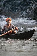 An Indian fisherman returns from a pre-dawn trip to check his nets out along the rocks of the Karnataka coast.