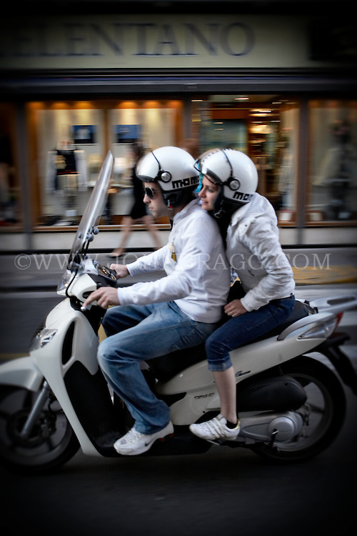 A couple riding an Italian scooter in Sorrento, Italy.