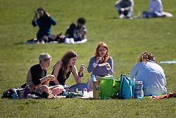 © Licensed to London News Pictures. 04/04/2021. London, UK. Members of the public relax and enjoy the warm weather in Greenwich Park in South East London. Temperatures are expected to rise with highs of 16 degrees forecasted for parts of London and South East England today . Photo credit: George Cracknell Wright/LNP