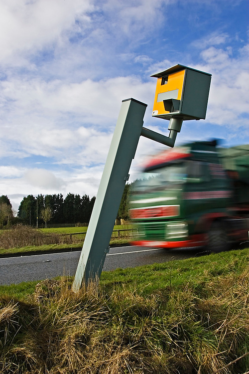 Traffic passes vandalised Gatso speed camera unable to function on A40 road, Oxfordshire, England, United Kingdom