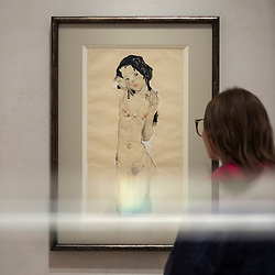 """© Licensed to London News Pictures. 31/10/2018. LONDON, UK. A visitor views """"Black-haired Nude Girl"""", 1910, by Egon Schiele. Preview of """"Klimt / Schiele:  Drawings from the Albertina Museum,Vienna"""" exhibition at the Royal Academy.  Over 100 works on paper are on display in an exhibition which marks the centenary of the deaths of the two most celebrated and pioneering figures of early twentieth-century art.  The show runs 4 November to 3 February 2019.  Photo credit: Stephen Chung/LNP"""