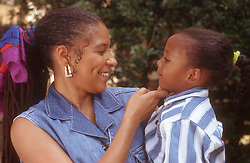 Mother standing outside holding young daughter smiling,