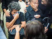 27 JANUARY 2014 - BANGKOK, THAILAND:  Mourners comfort Sarode Taratin, 77, left, and her husband, Likit Taratin, 80, the parents of Suthin Taratin during bathing rites for Suthin at Wat Sommanat Rajavaravihara in Bangkok. In Thai tradition, after death a bathing ceremony takes place in which relatives and friends pour water over one hand of the deceased. Suthin was a core leader of the People's Democratic Force to Overthrow Thaksinism (Pefot), one of several organizations leading protests against the elected government of Thai Prime Minister Yingluck Shinawatra. He was murdered Sunday, Jan. 28, while he was leading a rally to prevent voters from reaching a polling center in the Bang Na district of Bangkok.    PHOTO BY JACK KURTZ