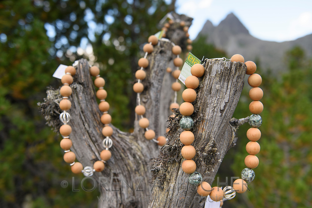 Close ups of Susanne Rösli's handcrafted necklaces  on a dead tree on a cloudy summer evening in July, Parc Ela, Grisons, Switzerland