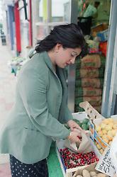 Woman choosing fruit at stall,