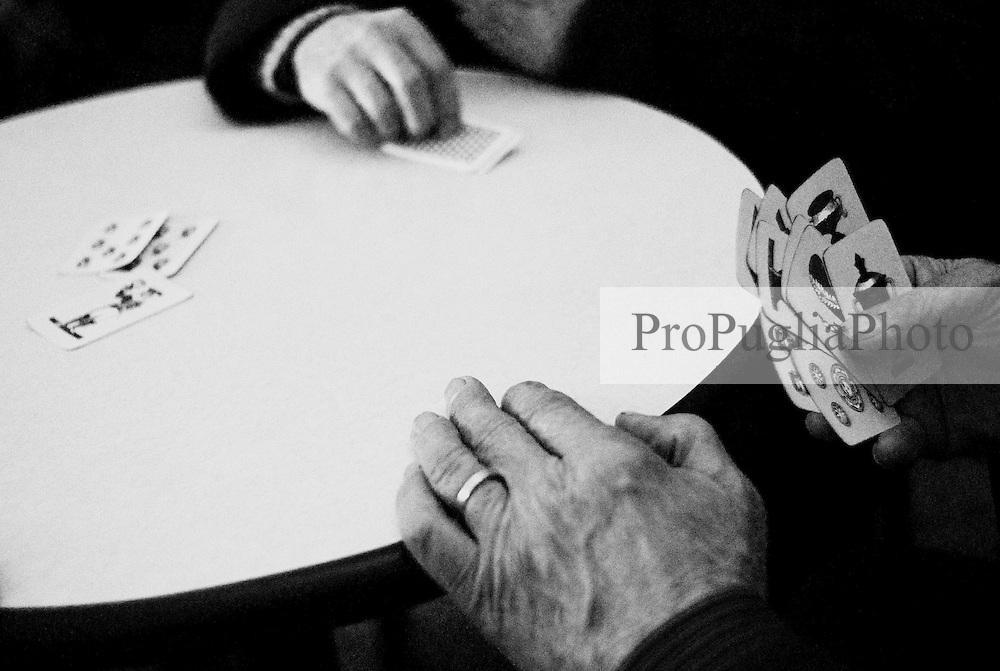 Reportage sviluppato ad Alessano (LE). Viene presa in considerazione fotograficamente, la gente che popola il paese nei suoi bar, piazze, strade, giardini pubblici. Ed, insieme a questa, i particolari caratterizzanti il luogo...uomini giocano a carte in un bar.