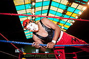 Male wrestler in mask climbing out of the ring. Lucha Libre wrestling origniated in Mexico, but is popular in other latin Amercian countries, including in La Paz / El Alto, Bolivia. Male and female fighters participate in the theatrical staged fights to an adoring crowd of locals and foreigners alike.