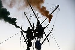 © Licensed to London News Pictures. 15/07/2021. Scunthorpe, UK.  Animal Rebellion activists let off flares from the top of bamboo poles as they set up a blockade at OSI Food Solutions in Scunthorpe. The food manufacturing company supply McDonald's restaurants, which Animal Rebellion accuse of mass exploitation of animals and environmental irresponsibility. Photo credit: Adam Vaughan/LNP