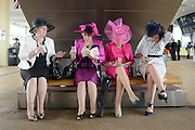 © Licensed to London News Pictures. 21/06/2012. Ascot, UK.  Women study race cards under an escalator.  Ladies Day at Royal Ascot 21st June 2012. Royal Ascot has established itself as a national institution and the centrepiece of the British social calendar as well as being a stage for the best racehorses in the world.. Photo credit : Stephen Simpson/LNP
