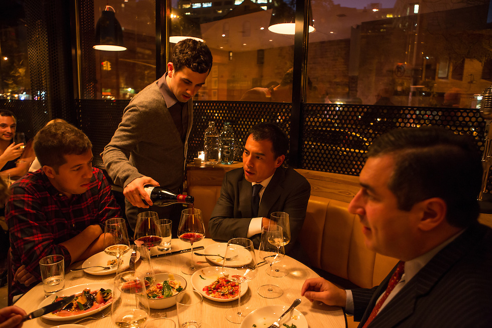 New York, NY, Sept. 30, 2013. Grant Reynolds, wine director at Charlie Bird, pouring for diners. (L to R) Bryan Garcia, Michael Liou and Juan Ruiz.