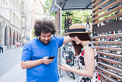Young couple text messaging on mobile phone in city