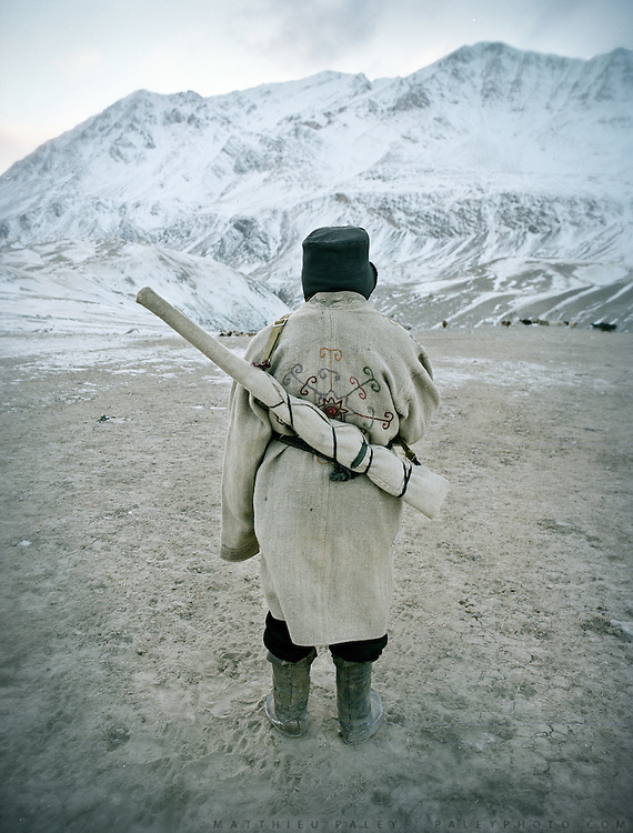 """Mohammad, Wakhi shepherd wearing traditional """"Chapan""""..Wakhi winter shepherds known as """"Shpunds"""" in their settlement of Kher Metek, on the edge of the Little Pamir. They often look over Kyrgyz sheep and yak herds for payment in animals. .Winter expedition through the Wakhan Corridor and into the Afghan Pamir mountains, to document the life of the Afghan Kyrgyz tribe. January/February 2008. Afghanistan"""