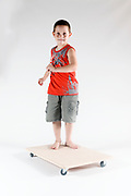 Indoor playground boy plays on wheeled board On white Background