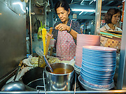 26 MAY 2015 - BANGKOK, THAILAND: A woman makes a noodle dish at her food cart on Sukhumvit Soi 38 in Bangkok. The food carts and small restaurants along Soi 38 have been popular with tourists and Thais alike for more than 40 years. The family that owns the land along the soi recently decided to sell to a condominium developer and not renew the restaurant owners' leases. More than 40 restaurants and food carts will have to close. The first wave of closings could start as soon June 21 and all of the restaurants are supposed to close over the next several months.     PHOTO BY JACK KURTZ